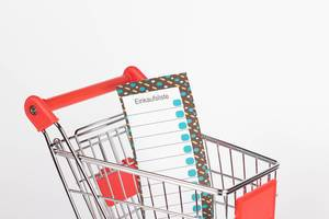 Leere Einkaufsliste in Einkaufswagen vor weißem Hintergrund