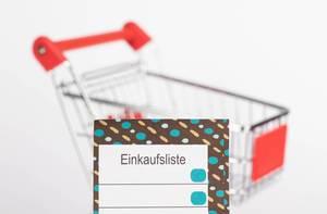Leere Einkaufsliste mit Einkaufswagen im Hintergrund mit Schärfentiefe fotografiert