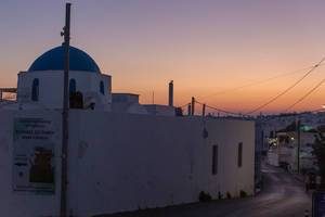 Leere Straße bei Nacht, mit orangem Himmel und weißer Kirche auf der griechischen Insel Paros