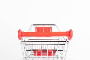 Leerer Einkaufswagen vor weißem Hintergrund aus der Perspektive des Kunden