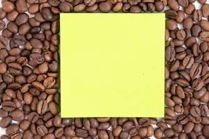 Leeres gelbes Post-it mit Platz für eigenen Text auf Hintergrund aus gerösteten Kaffeebohnen