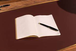 Leeres Heft mit edlem Kugelschreiber auf luxuriösem Tisch