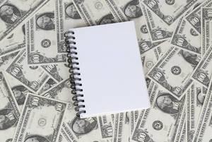 Leeres Notizbuch mit Ringbindung liegt auf 100 US-Dollar Noten