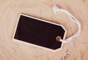 Leeres schwarzes Preisschild aus Holz für eigenen Text auf Baumstrunk