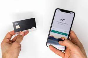 Left hand shows N26 Black bank card while right hand shows Iphone with the N26 mobile app