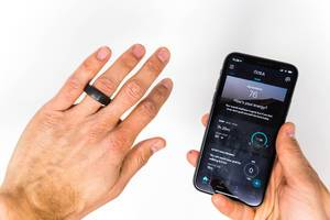 Left hand with Oura smart ring on finger, right hand shows phone with the Oura app´s energy and activity statistics