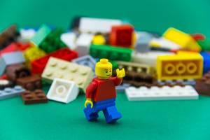 Legofigur läuft vor einem Haufen von  bunten Legosteinen