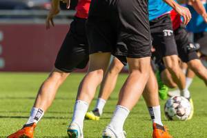 Legs of football players on a pitch during training