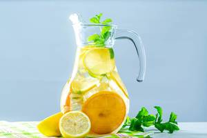 Lemonade pitcher with lemon, mint and ice on table