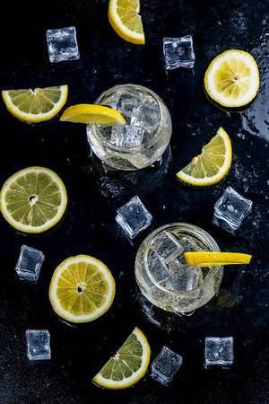 Lemonade with ice cubes and sliced lemon on black background. Top view (Flip 2019)