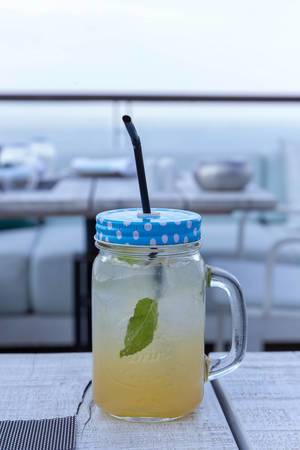 Lemonade with mint and ice in a half-liter glass with lid and drinking straw
