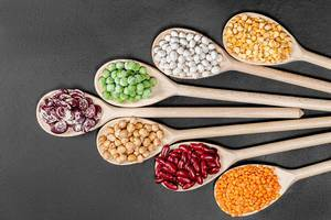 Lentils, chickpeas, peas and beans of different colors in wooden spoons on a black background. Top view (Flip 2019)