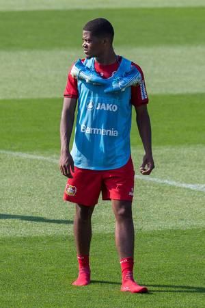 Leon Bailey in Socken auf dem Fußballfeld, mit umgehängten Fußballschuhen, während dem Mannschaftstraining