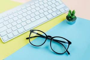 Lesebrille auf Computerzubehör auf farbenfrohem Schreibtisch