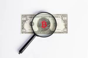 Leselupe über Bitcoin der auf 100-Dollarnote liegt mit weißem Hintergrund