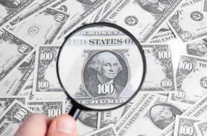 Leselupe vergrößert Portrait von Präsident George Washington auf 100-Dollar Banknote