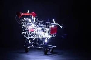 Leuchtender Einkaufswagen mit darin liegende Lichterketten für Weihnachtsbaum vor dunklem Hintergrund