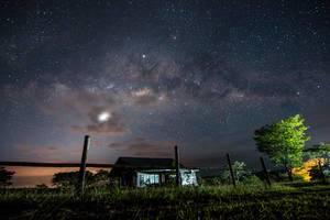 Leuchtender Sternenhimmel über in Feldern stehendem Haus in Don Salvador, Philippinen