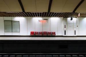 """Leuchtendes Neonschild der """"Omonia"""" U-Bahn Station über roten Stühlen am Bahnsteig in Athen, Griechenland"""