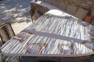 Licht-und Schattenspiel auf einem gedeckten Tisch auf der Außenveranda eines Restaurants auf Paros, Griechenland