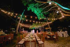 Lichterketten überdachen die Tische einer Hochzeit bei Nacht in Punta Bulata