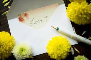 Liebesnotiz in einem Umschlag mit Stift und Blumen