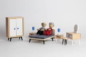 Liebliches Großelternpaar liegt in Miniatur-Puppenbett neben voller Schlafzimmereinrichtung - Nahaufnahme