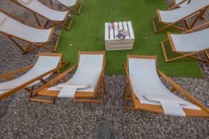 Liegestühle auf Kunstrasen bilden eine Runde
