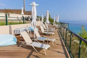 Liegestühle und Sonnenschirme auf einer Hotelterrasse mit Blick aufs Meer