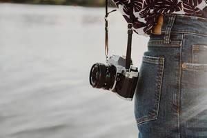 Lifestyle-Foto eines Mädchens mit einer klassischen Filmkamera. Meer im Hintergrund