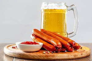 Light beer with grilled sausages and ketchup