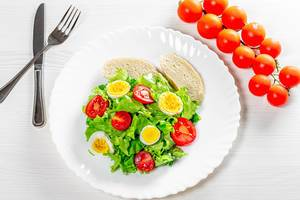 Light salad with herbs, tomatoes, boiled eggs and breadcrumbs on a white table (Flip 2019)