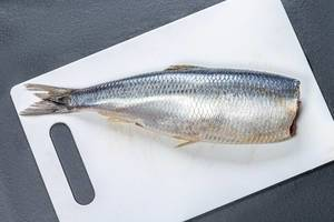 Lightly salted herring on a white kitchen Board. Top view (Flip 2019)