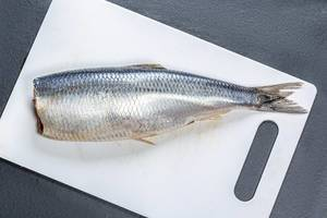 Lightly salted herring on a white kitchen Board. Top view