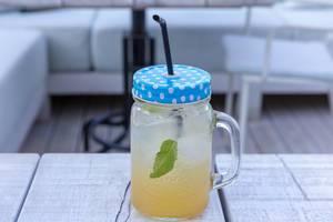 Limonade mit Minze und viel Eis in einem Halbliterglas mit Deckel und Trinkhalm