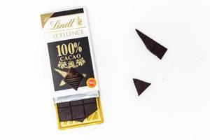 Lindt Excellence 100% Kakao Schokoladentafel, schon angebrochen mit losen Schokoladenstücke vor weißem Hintergrund