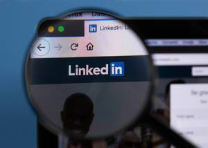 Linkedin logo on a computer screen with a magnifying glass