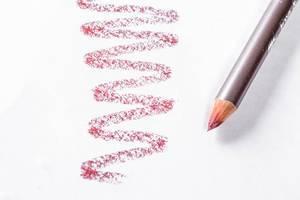 Lippenkonturstift in dezentem Dunkelrot mit Farbprobe auf weißem Papier