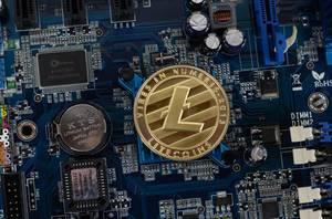 Litecoin Kryptowährung Silbermünze auf dem Chip auf der Hauptplatine eines Computers