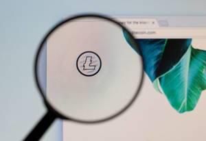 Litecoin-Logo am PC-Monitor, durch eine Lupe fotografiert