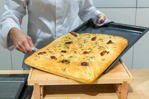 Live cooking show by Miele with German TV-chef Bettina Seitz at IFA in Berlin: Focaccia - Ligurian flatbread with herbs on a baking tray