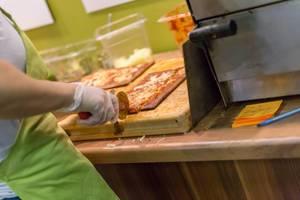 Lizza Low-Carb Pizza wird in kleine Stücke geschnitten