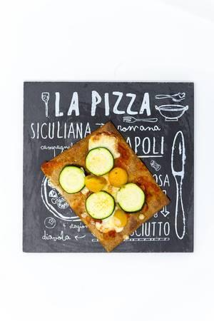 Lizza Veganer low carb Pizzaboden aus Chia und Leinsamen mit gelben Kirschtomaten, Zucchini und Käse