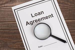 Loan Agreement document with magnifying glass