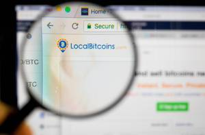 Localbitcoins-Logo am PC-Monitor, durch eine Lupe fotografiert