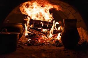 Loderndes Feuer in steinernem Ofen mit Töpfen