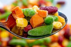 Löffel mit Erbsen, Mais, Bohnen und Karotten in der Nahaufnahme