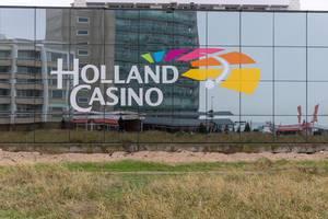 Logo des Holland Casinos auf der verglasten Fassade mit Spiegelung der Umgebung
