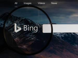 Logo und Schriftzug der Suchmaschine Bing, vergrößert durch eine Lupe dargestellt
