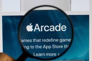 """Logo und Schriftzug des Spielediensts """"Apple Arcade"""",  vergrößert durch eine Lupe dargestellt"""